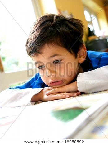 Young boy engross in reading his book, indoor.