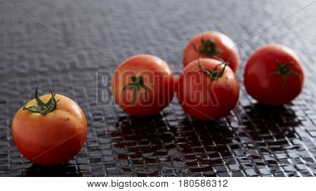 Fresh Red Tomatoes On Black Tile Floor