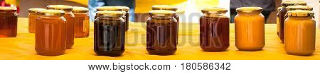 honey jars in a row on a yellow table