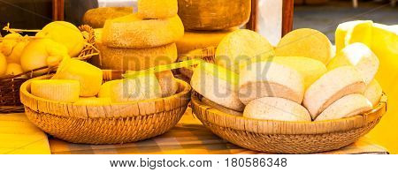 wheels of cheese and dairy products in wicker baskets