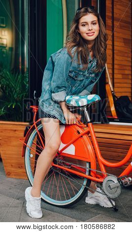 A stunner young girl in fashionable denim jacket sits on the trunk of a red vintage bicycle on a background of a summer outdoor cafe on a warm evening. Outdoor. LA. California.