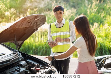 Asian insurance agent and Asian woman stressed at Roadside After Traffic Accident Asian insurance agentexamining car after accident