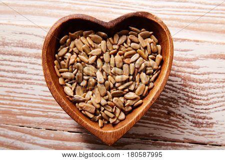 Sunflower seeds in a wooden heart shape bowl on wood board