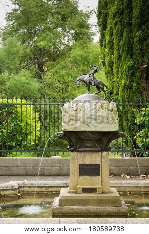 Auckland New Zealand - March 1 2017: Valkyrie Fountain features bronze statue of fierce and energetic Valkyrie rider on protesting horse. White decorated stand with frieze. Green tree background