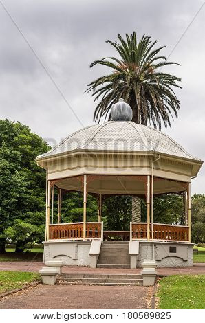 Auckland New Zealand - March 1 2017: The octagonal yellow band stand in the Domain has a dome where over a large palm tree peaks. More green vegetation under cloudy gray sky.