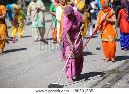 Vicenza, Vi, Italy - April 8, 2017: Sikh Religious  Barefoot Women Sweeping The Street With Brooms D