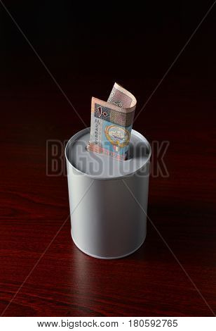 Ten Kuwaiti Dinar note inserted in the saving can. Saving can with Ten KWD note.