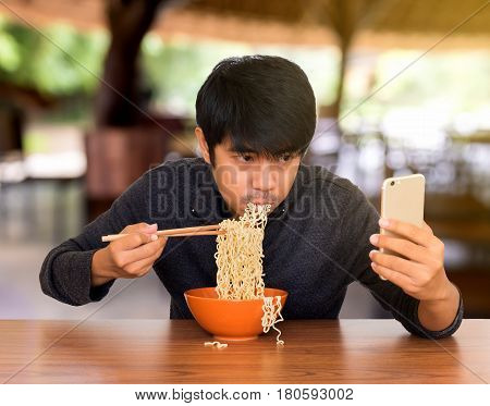 Man eating chinese noodle monstrously whilst looking and using smartphone. Concept of smartphone addiction phubbing or social network issues