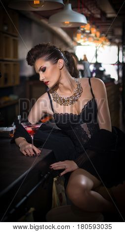Sensual girl with long legs and high heels sitting on the chair in bar  drinking .Handsome girl wearing beautiful body and high heels in indoor scene.Fashion model with long sexy legs drink cocktail.