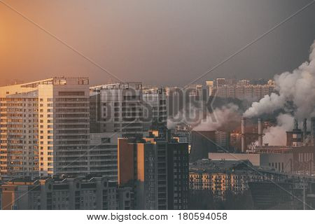 Close-up shooting from high point of metropolitan city: residential buildings and districts illuminated by morning sun smoke and chimneys of combined heat and power plant polluting environment