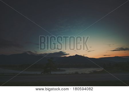 Dramatic wide angle view of village dirt road in foreground near Katun mountain river on late sunset with mountains and hills in background pine tree and dark scenery teal summer sky Altai Russia