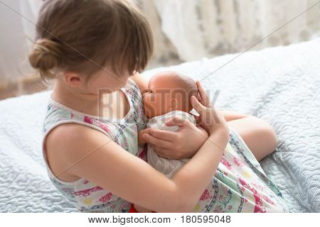 Kid girl playing with a doll playing in breastfeeding taking care of a doll life style and childhood