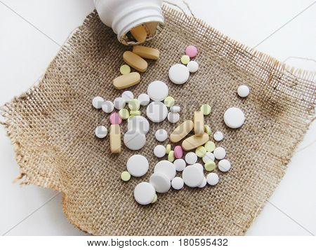 Pills and vitamins pouring out of the white bottle. Colorfull medicine, health care, pharmacy, prescription for treatment, medication concept