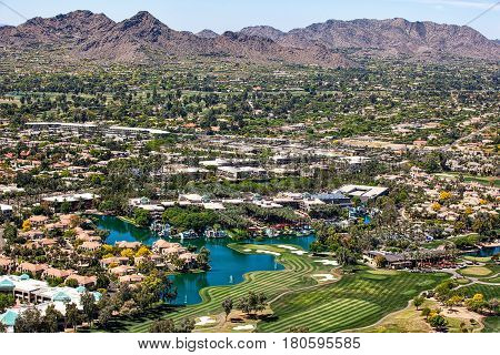 Over Scottsdale Arizona looking to the southwest at golf courses resorts luxury homes and Mummy Mountain