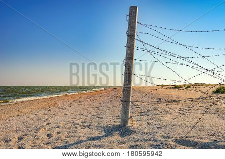 Access of dunes to the beach towards the sea with a fence with barbed wire at sunset