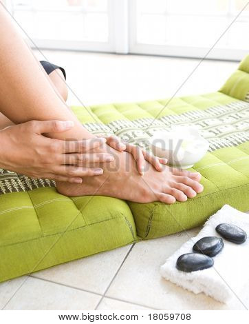 Woman pampering her feet, treating it with aroma therapy and therapy stones