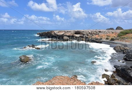 The ocean swirling off the coast of Aruba's black sand stone beach.