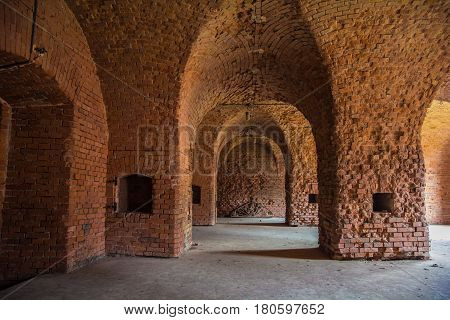 Arched corridors of the old fortification structure of red brick