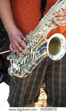 Alto saxophone being played by a jazz musician performing in concert outside.