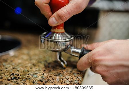Closeup barista grinding fresh coffee into bayonet. poster
