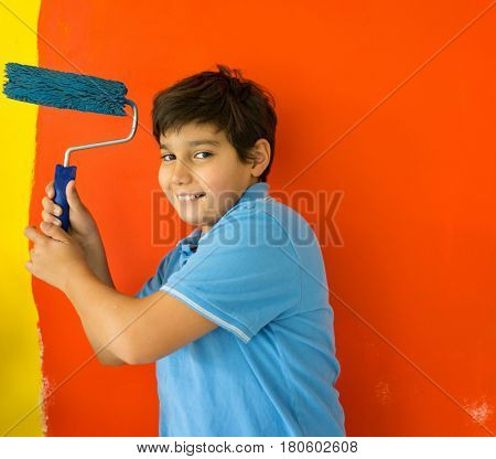 Adorable boy in bright paint with mess of paint child on wall