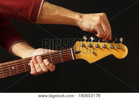 Hands tunes the guitar on the black background