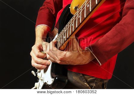 Guitarist put fingers for chords on electric guitar on the black background