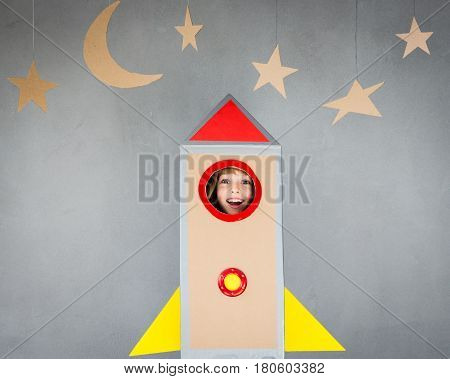 Kid Playing With Cardboard Rocket At Home