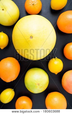 Lemon, orange, mandarin, grapefruit, sweetie and pomelo on black background. Flat lay, top view.