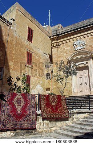 Oriental carpets hanging on a railing beside a church
