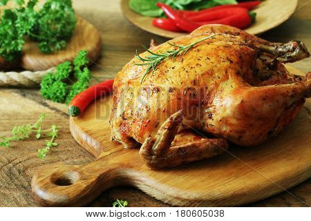 Whole roasted chicken with herb on cutting board