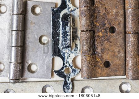 Old vintage locks and door hinges rusted and frayed with peeling paint spread out in order on a light wooden background close up