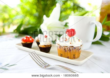 Pretty cupcakes in white plate served with cup of coffee, outdoor setting