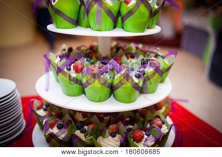 mini cupcakes on a multi level tier in different colors. cute and colorful yummy cupcakes tier