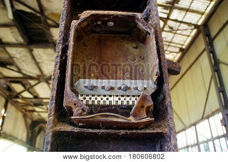 Old brown rusty switches in control box ruins of factory