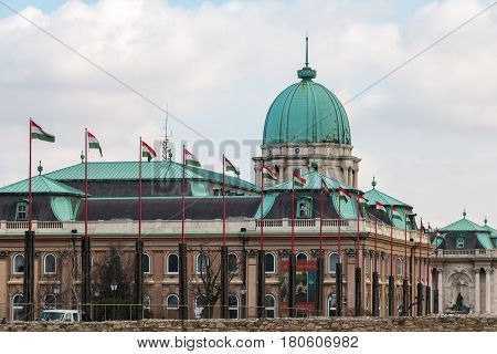 Budapest, Hungary - March 09, 2017: National hungarian waving flags in front of Royal palace building in Buda castle
