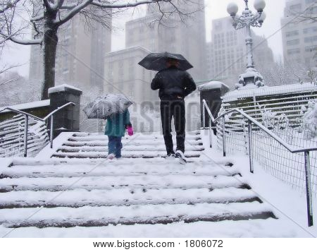 Small Girl And Man Walking In Snow In Nyc