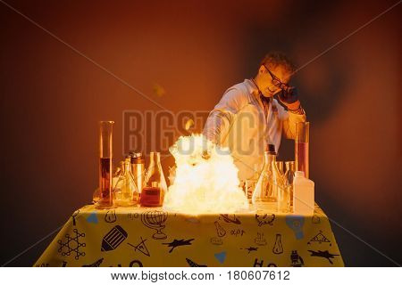 Professor in the laboratory, conducting chemical experiments with fire and explosions. On the table fire and various tubes