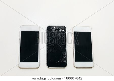 one black broken phone and two white whole next. Are on the table, two white sides black.