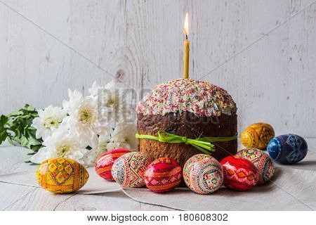 Easter cake kulich with eggs and spring flowers on light wooden background.