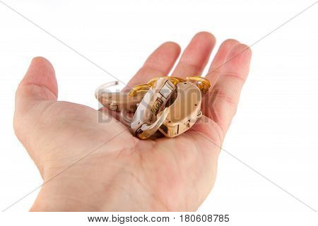 Hand showing used and old hearing aids. Isolated on white.
