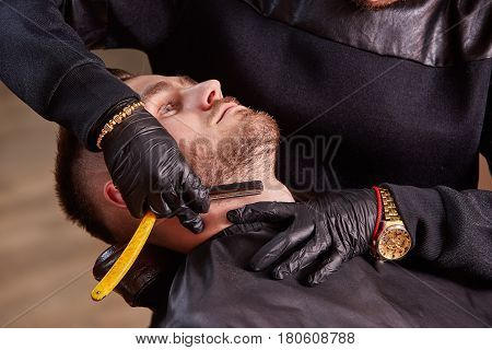 Master makes beards correction with shaver in barbershop salon. Close up photo. Black clothes and black cape. Professionalism and craftsmanship. Barbershop concept. Male fashion.