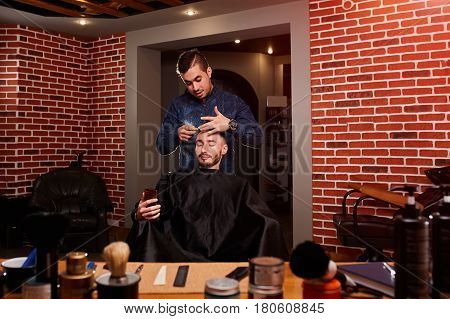Young handsome barber combing attractive man while sitting at the chair and looking at phone in barbershop. Background is the brick wall. Two man. Professionalism and craftsmanship.