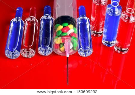 Syringe for subcutaneous injections with glass ampoules and multicolored tablets on an isolated background. Ampoule. Syringes