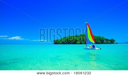 Family enjoying a ride in the sailboat at beautiful tropical sea