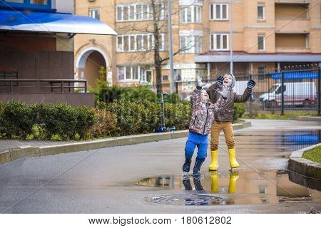 Two Little Boys, Squat On A Puddle, With Little Umbrellas