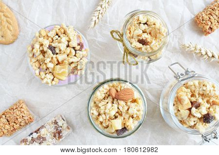 fruit crunchy and muesli with yogurt in the jars on the table, top view background, healthy food concept