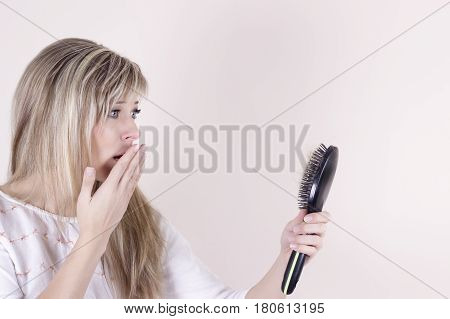 Hair loss. Depressed young woman looking at her hairbrush and expressing negativity.