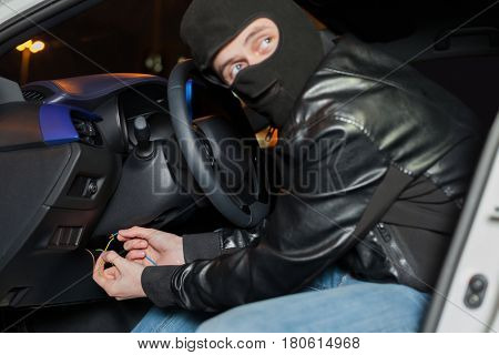 Male car thief breaks the ignition switch