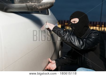 Male thief trying to open car door